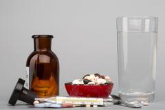 各种各样的药片、医疗瓶和杯水 免版税库存照片