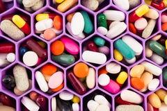 各种各样的药片和胶囊在多孔的梳子组织者 库存图片