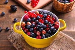 各种各样的莓果包括蓝莓、莓、黑莓无核小葡萄干和鹅莓在一个黄色碗在一棕色woode 库存图片