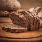 各种各样的被烘烤的面包和卷在土气木桌上 免版税库存照片