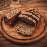 各种各样的被烘烤的面包和卷在土气木桌上 免版税图库摄影