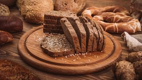 各种各样的被烘烤的面包和卷在土气木桌上 库存照片