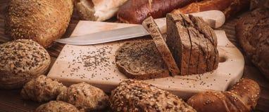 各种各样的被烘烤的面包和卷在土气木桌上 库存图片