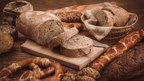 各种各样的被烘烤的面包和卷在土气木桌上 图库摄影