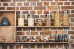 各种各样的谷物和香料在玻璃容器在木架子 库存图片