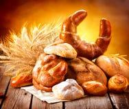 各种各样的面包和捆麦子耳朵 图库摄影