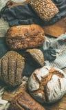 各种各样的面包大面包平位置在灰色背景,顶视图的 免版税库存图片