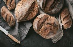 各种各样的面包选择平位置  在洗碗布的Multigrain土气面包在灰色背景,顶视图,拷贝空间 免版税库存照片