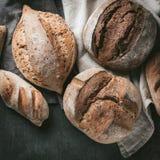 各种各样的面包选择平位置  在洗碗布的Multigrain土气面包在灰色背景,顶视图,拷贝空间 库存图片