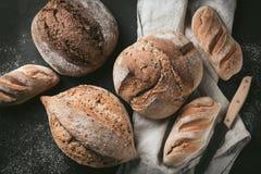 各种各样的面包选择平位置  在洗碗布的Multigrain土气面包在灰色背景,顶视图,拷贝空间 免版税库存图片
