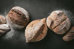 各种各样的面包选择平位置 在灰色背景的Multigrain土气面包 顶视图,拷贝空间 水平的构成 免版税库存照片