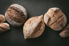 各种各样的面包选择平位置 在灰色背景的Multigrain土气面包 顶视图,拷贝空间 水平的构成 免版税库存图片