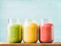 各种各样的颜色和口味新鲜的被混和的果子圆滑的人在玻璃瓶子 绿色,黄色,红色 库存照片