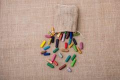 各种各样的颜色蜡笔在大袋外面的 图库摄影
