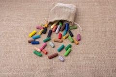 各种各样的颜色蜡笔在大袋外面的 免版税图库摄影