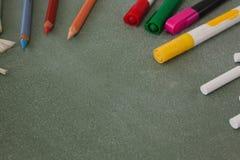各种各样的颜色铅笔、记号笔和白垩在黑板 免版税库存照片