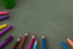 各种各样的颜色铅笔和记号笔在黑板 免版税库存照片