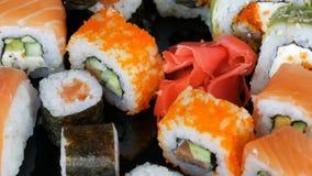 各种各样色的寿司卷集合和姜转动在黑背景的镜子表面上 日本烹调 股票视频