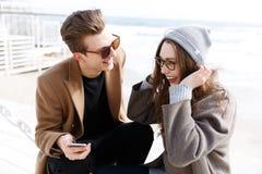 结合一起笑和使用智能手机户外在秋天 库存照片