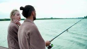 结合一起钓鱼在湖、风在头发,谈话的男孩和的女孩,当钓鱼在转动时 股票录像