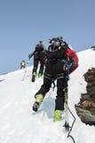 合作上升在绳索的山的滑雪登山家 免版税图库摄影