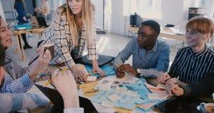 合作与不同种族的雇员的成功的愉快的白种人女性创造性的组长在健康办公室会议上 股票录像