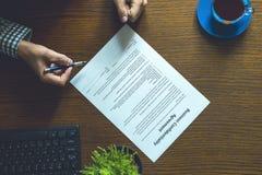 合作协议商业文件由在桌上的一个人签了字在办公室 库存图片