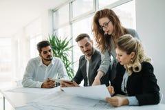 合作和分析由工作在办公室的商人 免版税库存照片