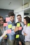 合作和分析由工作在办公室的商人 库存照片