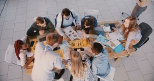 合作在现代办公室的顶视图小组专业不同种族的商人专家,配合概念 股票视频