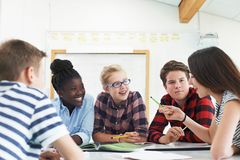 合作在项目的小组少年学生在教室 库存照片