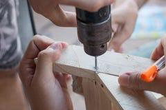合作在钻木制品与电钻 免版税库存照片