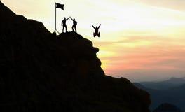 合作工作、生活目标和自我改善概念 供以人员帮助他的山的一个陡峭的边缘的女性上升的伙伴 库存照片