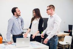 合作是钥匙对成功 谈论三个年轻的商人某事,当看计算机时 库存图片