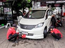合作服务技工清洁汽车汽车在自动洗涤汽车 免版税库存照片