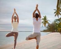 结合做瑜伽锻炼在海滩由后面 免版税库存照片