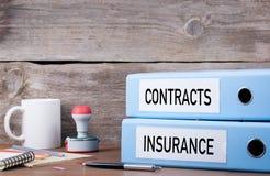 合同和保险 在书桌上的两种黏合剂在办公室 Busi 免版税库存照片