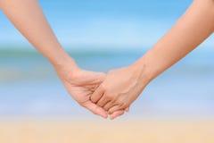 结合在一起使手和海背景的朋友 免版税库存照片