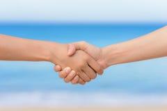 结合在一起使手和海背景的朋友 免版税库存图片
