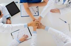结合在一起使手的小组医生在桌上 库存图片