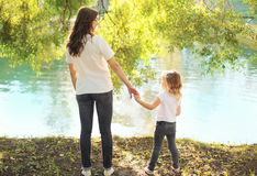 结合在一起使手的愉快的母亲和儿童女儿在夏天 库存图片