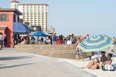 结合在伞下坐海滩木板走道 免版税库存照片