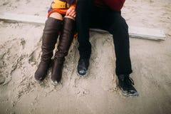 结合坐沙子在冬天海滩 半身纵向 在行家鞋子的夫妇的腿关闭  免版税库存图片