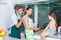 结合女孩,父亲母亲和女儿烹调 免版税库存图片