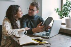 结合工作在与片剂,膝上型计算机,智能手机,笔记薄的咖啡馆 免版税库存照片