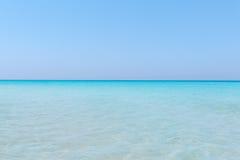 合并与清楚的美丽的天空的绿松石平静的海洋在天际线在晴朗的温暖的天 免版税库存照片