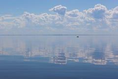 合并与被覆盖的天空的风平浪静的深刻的蓝色表面 Th 图库摄影