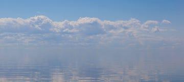 合并与被覆盖的天空的风平浪静的深刻的蓝色表面 Th 免版税图库摄影