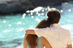 结合拥抱和观看海在度假 免版税库存图片