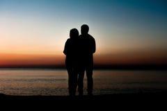 结合拥抱在爱的男人和妇女停留在海滩 免版税库存图片